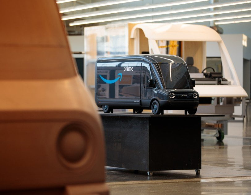 Un modello in scala del nuovo veicolo elettrico Amazon decorato con un logo sorriso si trova tra due modelli più grandi del veicolo.